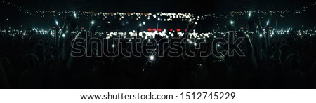 Photo of Big concert crowd background.Silhouette of many young people with smartphones lights in hands having fun on popular musical event in huge music hall.Festival audience wave hands to famous rock singer