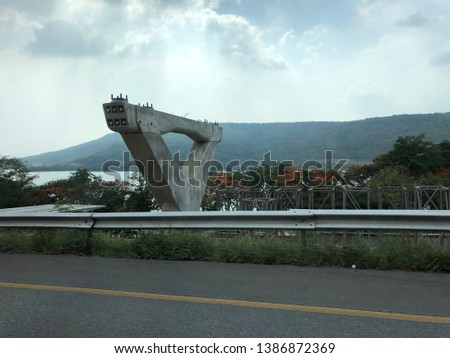 Big concrete post in nature background.  Construction of motorway road near river and mountain backdrop.Motorway construction zone.Large concrete post on sky background.