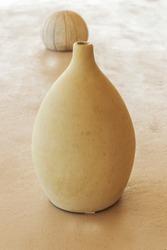 big cream vertical ceramic vase on the table