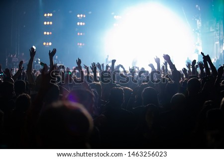 Big crowd of excited music fans waving hands to favorite musical tracks on edm dj concert in nightclub.Youth entertainment event background.Happy people partying on dance floor in bright stage lights