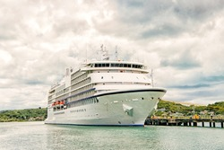 big cruise ship, beautiful white yacht, luxury modern motor vehicle at moorage in caribbean sea port, pier in st. john, Antigua, shore or bay on summer day on cloudy sky background