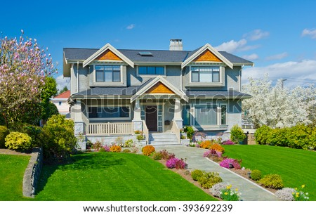 Big custom built luxury  home with nicely trimmed and landscaped front yard in the suburbs of Vancouver, Canada.