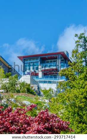 Big custom built luxury modern house on the rocks, cliff with nicely landscaped front yard in the residential neighborhood of Vancouver, Canada. Vertical.