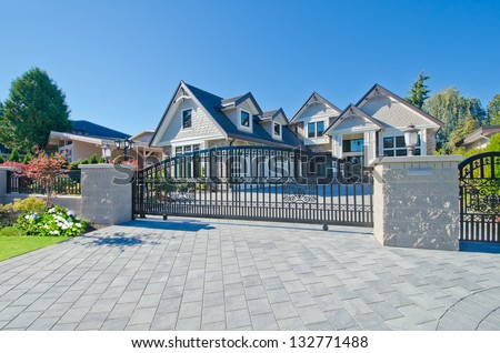 Big custom made luxury house behind the gates and nicely paved driveway in the suburbs of Vancouver, Canada.