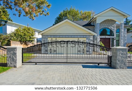 Big custom made luxury house with double doors garage behind the gates in the suburbs of Vancouver, Canada.