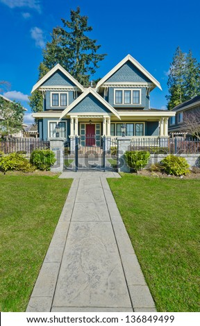 Big custom made luxury house with long doorway and nicely trimmed front yard in the suburbs of Vancouver, Canada. Vertical.