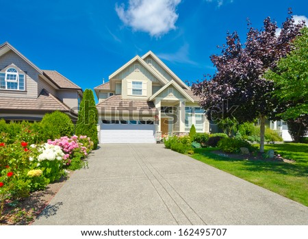 Big custom made luxury house with long driveway and nicely landscaped front yard in the suburbs of Vancouver, Canada.