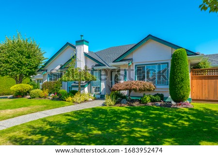 Big custom made luxury house with nicely landscaped and trimmed front yard and driveway to garage. Stock photo ©