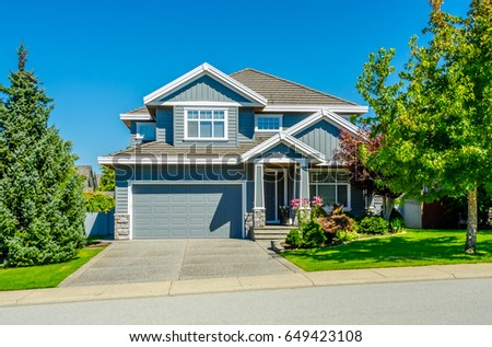 Big custom made luxury house with nicely landscaped and trimmed front yard and driveway to garage in the suburbs of Vancouver, Canada. #649423108