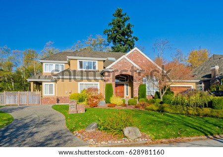 Big custom made luxury house with nicely landscaped and trimmed front yard in the suburbs of Vancouver, Canada. #628981160