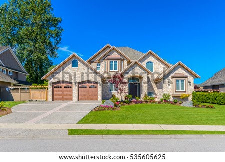 Big custom made luxury house with nicely landscaped front yard and driveway to garage in the suburbs of Vancouver, Canada. #535605625