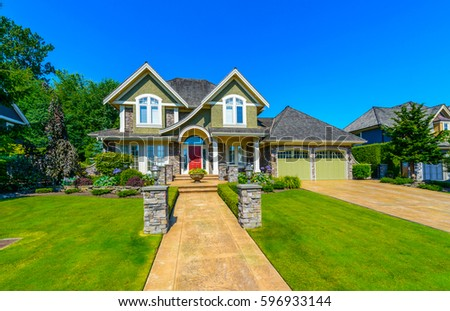 Big custom made luxury house with nicely landscaped front yard and driveway to garage in the suburbs of Vancouver, Canada. #596933144