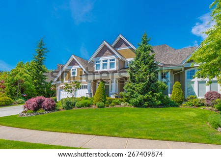 Big custom made luxury house with nicely landscaped front yard and driveway to garage in the suburb of Vancouver, Canada.