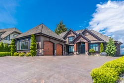 Big custom made luxury house with nicely landscaped front yard and long and wide paved driveway to the triple doors garage in the suburb of Vancouver, Canada.