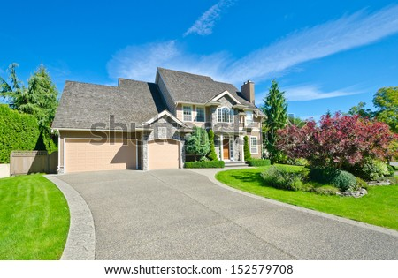 Big custom made luxury house with nicely landscaped front yard and long driveway in the suburbs of Vancouver, Canada.