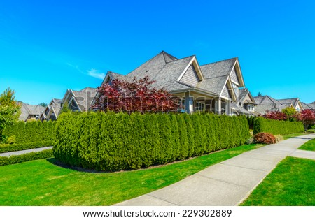 Big custom made luxury house with nicely landscaped front yard behind green fence  in the suburbs of Vancouver, Canada.