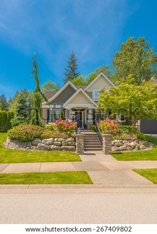 Big custom made luxury house with nicely landscaped front yard in the suburb of Vancouver, Canada.