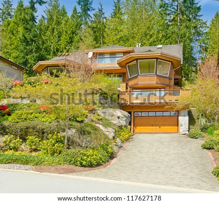 Big custom made luxury house with nicely landscaped front yard in the suburbs of North Vancouver, Canada.