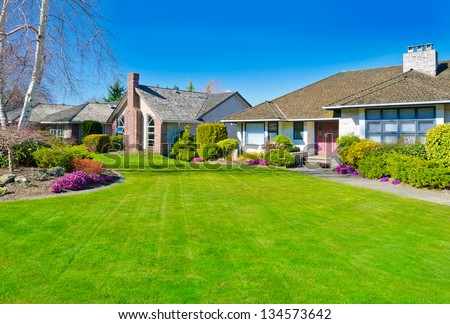 Big custom made  luxury house with nicely landscaped front yard, lawn in the suburbs of Vancouver, Canada.
