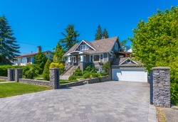 Big custom made luxury house with nicely paved driveway to the double doors garage in the suburb of Vancouver, Canada.