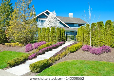 Big custom made luxury house with nicely trimmed and landscaped doorway and front yard lawn in the suburbs of Vancouver, Canada.