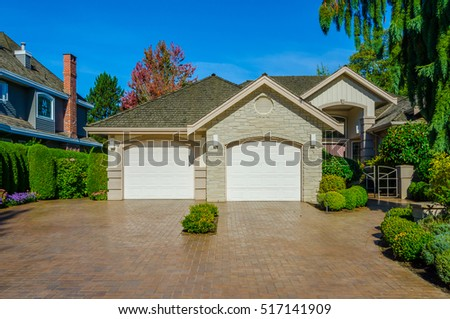Big custom made luxury house with nicely trimmed and landscaped front yard and driveway to garage in the suburbs of Vancouver, Canada. #517141909