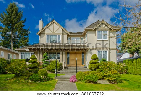 Big custom made luxury house with nicely trimmed and landscaped front yard in suburbs of Vancouver, Canada. #381057742