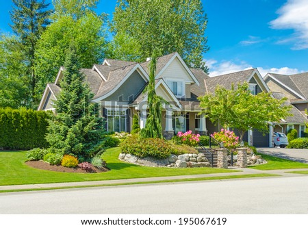 Big custom made luxury house with nicely trimmed and landscaped front yard  in the suburb of Vancouver, Canada.g