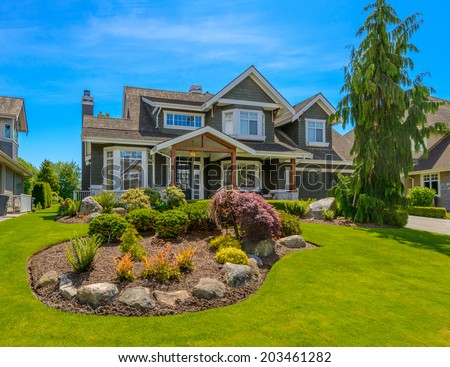 Big custom made luxury house with nicely trimmed and  landscaped front yard in the suburb of Vancouver, Canada. Landscape design.