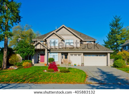 Big custom made luxury house with nicely trimmed and landscaped front yard in the suburb of Vancouver, in colorful fall time. Canada. #405883132