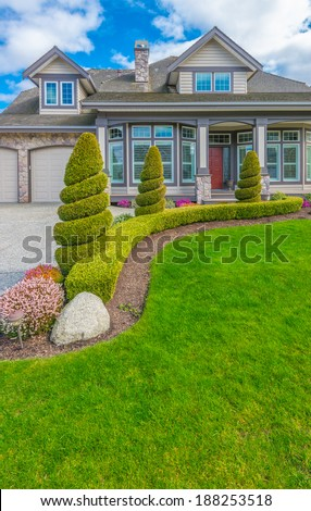 Big custom made luxury house with nicely trimmed and landscaped front yard in the suburbs of Vancouver, Canada. Landscape design. Vertical.
