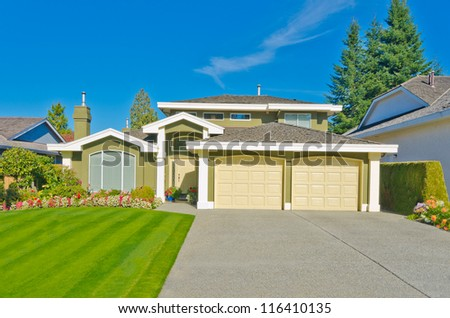 Big custom made luxury house with nicely trimmed lawn, front yard and long driveway in the suburbs of Vancouver, Canada.