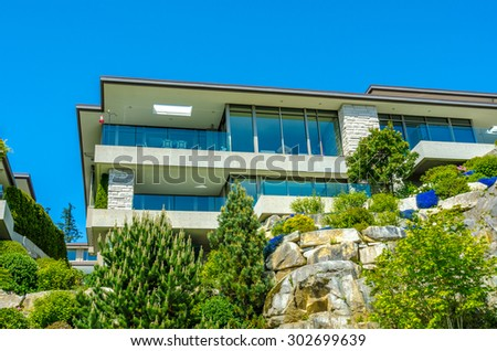 Big custom made luxury modern house on the rock with nicely landscaped front yard in the suburbs of Vancouver, Canada.