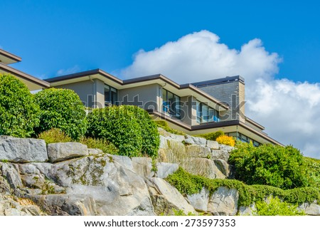 Big custom made luxury modern house on the rocks with nicely landscaped front yard in the suburbs of Vancouver, Canada.