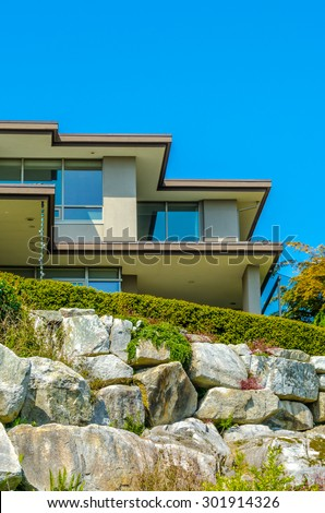 Big custom made luxury modern house on the rocks with nicely landscaped front yard in the suburbs of Vancouver, Canada. Vertical.