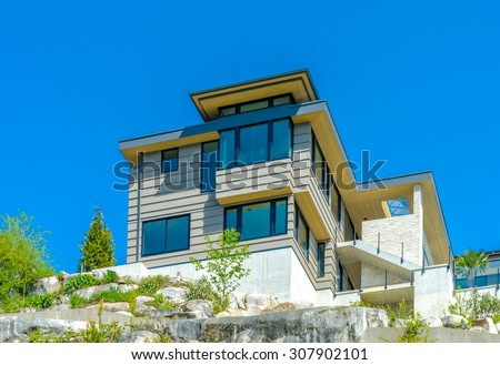 Big custom made luxury modern house under final stage of construction on the rock with nicely landscaped front yard in the suburbs of Vancouver, Canada.
