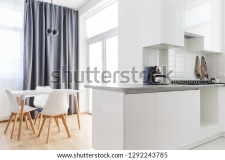 Big dining room with the kitchen wall on the right side and the table with the chairs on the left side. #1292243785