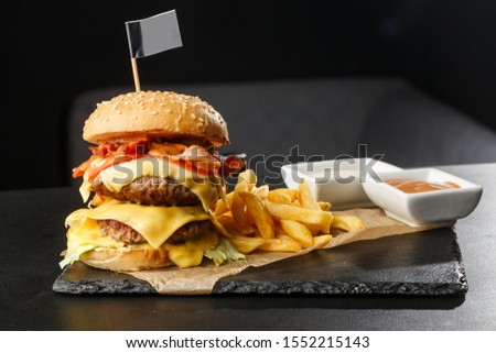 Big double cheeseburger with french fries isolated on black background. hamburger with beef patty , bacon, onion, tomato, lettuce pickles, aged cheddar, mustards, tomato jam, mayo. Horizontal Stock photo ©