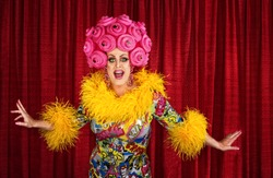 Big drag queen performing a song in theater