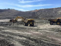 Big dump truck loaded by an excavator view on coal mine area