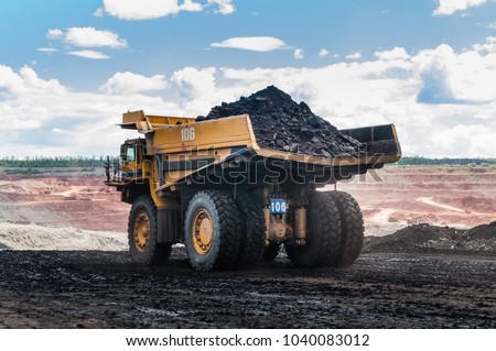 Big dump truck or Mining truck is mining machinery, or mining equipment to transport coal from open-pit or open-cast mine as the Coal Production. This picture show dump truck on open-pit coal mine.