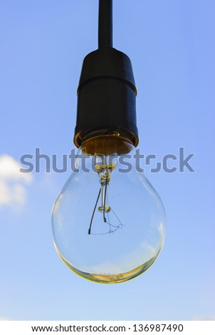 Big electric bulb with sky background - stock photo