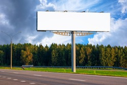 Big empty mockup Billboard along a highway with forest on background of blue sky with beautiful clouds.