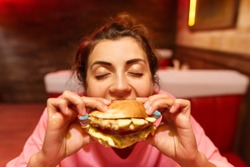 Big-eyed brunette girl is very seductive and with a big appetite is eating a harmful but very tasty hamburger