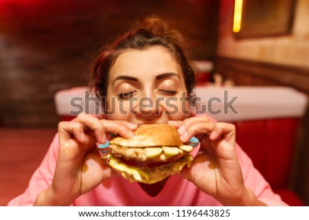 Big-eyed brunette girl is very seductive and with a big appetite is eating a harmful but very tasty hamburger #1196443825