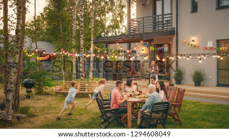 Big Family Garden Party Celebration, Gathered Together at the Table Family, Friends and Children. People are Drinking, Passing Dishes, Joking and Having Fun. Kids Run Around Table.