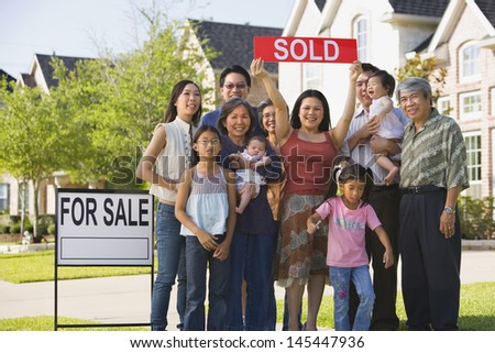 Big family holding up Sold sign in front of house
