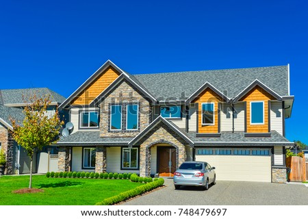 Big family house with double size garage and car parked in front. Residential house with concrete driveway and entrance door under the porch