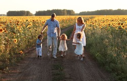 big family mom dad twins girls and son walking among sunflowers and happy smiling