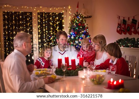 Big family with three children celebrating Christmas at home. Festive dinner at fireplace and Xmas tree. Parent and kids eating at fire place in decorated room. Child lighting advent wreath candle. #316221578